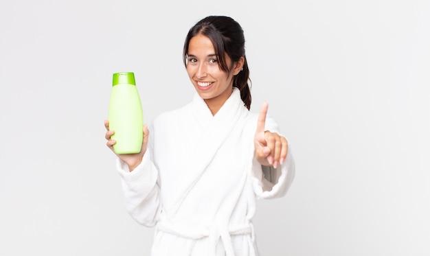 Młoda latynoska kobieta uśmiecha się dumnie i pewnie robi numer jeden w szlafroku i trzyma szampon