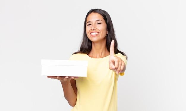 Młoda latynoska kobieta uśmiecha się dumnie i pewnie robiąc numer jeden