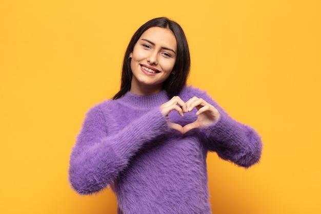 Młoda latynoska kobieta uśmiecha się i czuje się szczęśliwa, urocza, romantyczna i zakochana, tworząc kształt serca obiema rękami