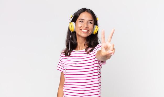 Młoda latynoska kobieta uśmiecha się i wygląda na szczęśliwą, gestykulując zwycięstwo lub pokój, słuchając muzyki przez słuchawki
