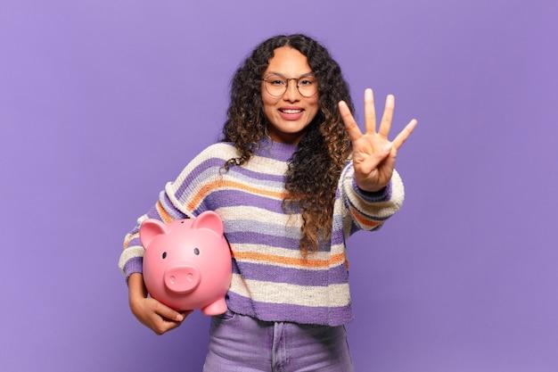 Młoda latynoska kobieta uśmiecha się i wygląda przyjaźnie, pokazując cyfrę cztery lub czwartą z ręką do przodu, odliczając w dół