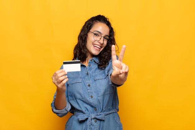Młoda latynoska kobieta uśmiecha się i wygląda przyjaźnie, pokazując numer dwa lub drugi z ręką do przodu, odliczając w dół
