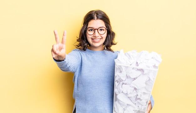 Młoda latynoska kobieta uśmiecha się i wygląda przyjaźnie, pokazując numer dwa nieudany koncept śmieci