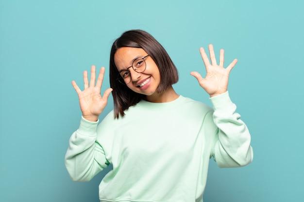 Młoda latynoska kobieta uśmiecha się i wygląda przyjaźnie, pokazując numer dziesięć lub dziesiątą z ręką do przodu, odliczając w dół