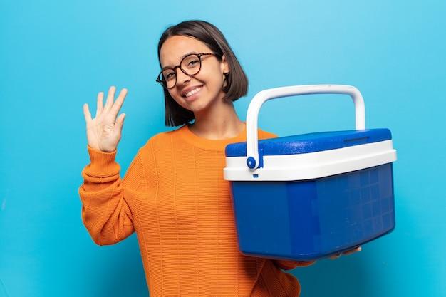 Młoda latynoska kobieta uśmiecha się i wygląda przyjaźnie, pokazując numer pięć lub piąty z ręką do przodu, odliczając w dół