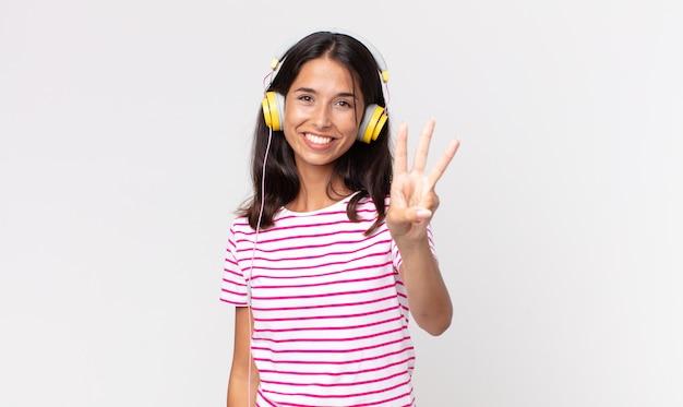 Młoda latynoska kobieta uśmiecha się i wygląda przyjaźnie, pokazując numer trzy słuchając muzyki przez słuchawki