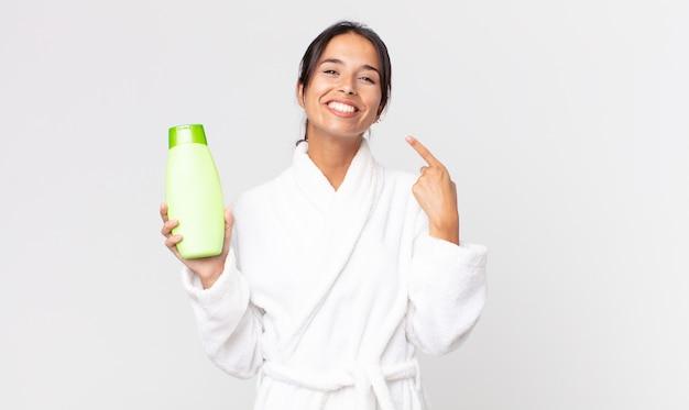 Młoda latynoska kobieta uśmiecha się pewnie, wskazując na swój szeroki uśmiech, ubrana w szlafrok i trzymająca szampon