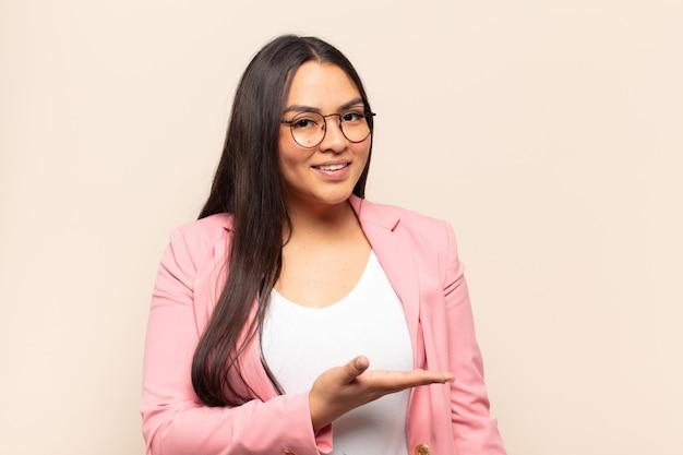Młoda latynoska kobieta uśmiecha się radośnie, czuje się szczęśliwa i pokazuje koncepcję w przestrzeni kopii z dłonią