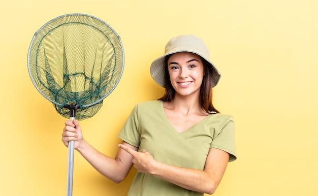 Młoda latynoska kobieta uśmiecha się radośnie, czuje się szczęśliwa i wskazuje na boczną koncepcję sieci rybackiej