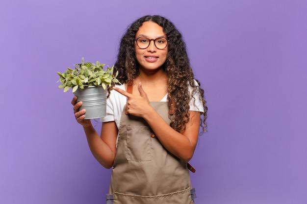 Młoda latynoska kobieta uśmiecha się radośnie, czuje się szczęśliwa i wskazuje na bok i do góry, pokazując obiekt w przestrzeni kopii. koncepcja ogrodnika