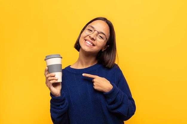 Młoda latynoska kobieta uśmiecha się radośnie, czuje się szczęśliwa i wskazuje na bok i do góry, pokazując obiekt w przestrzeni kopii