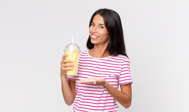 Młoda latynoska kobieta uśmiecha się radośnie, czuje się szczęśliwa, pokazuje koncepcję i trzyma koktajl mleczny o smaku waniliowym