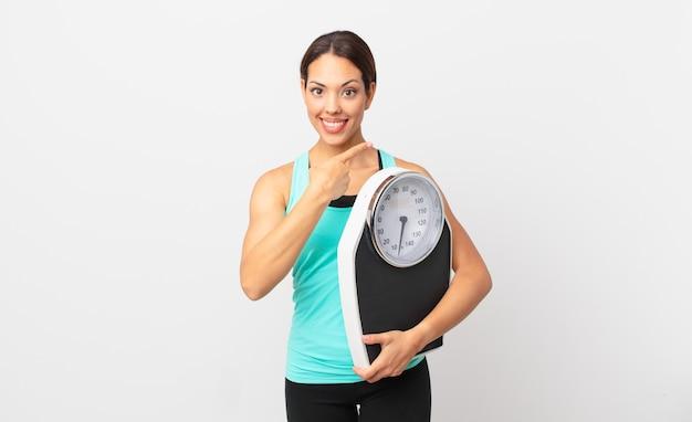 Młoda latynoska kobieta uśmiecha się radośnie, czuje się szczęśliwa, wskazuje na bok i trzyma wagę