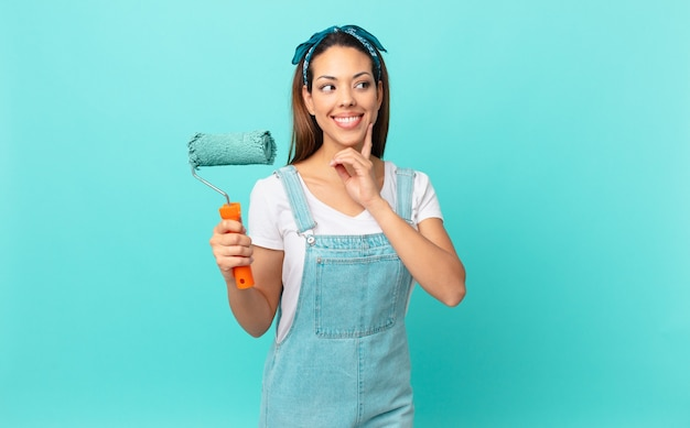 Młoda latynoska kobieta uśmiecha się radośnie i marzy lub wątpi i maluje ścianę