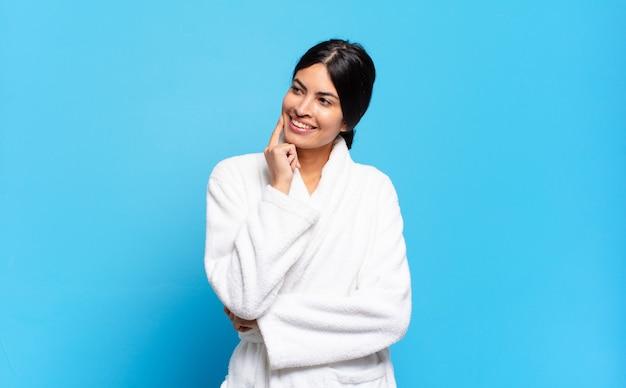 Młoda latynoska kobieta uśmiecha się radośnie i marzy lub wątpi, patrząc w bok. koncepcja szlafrok