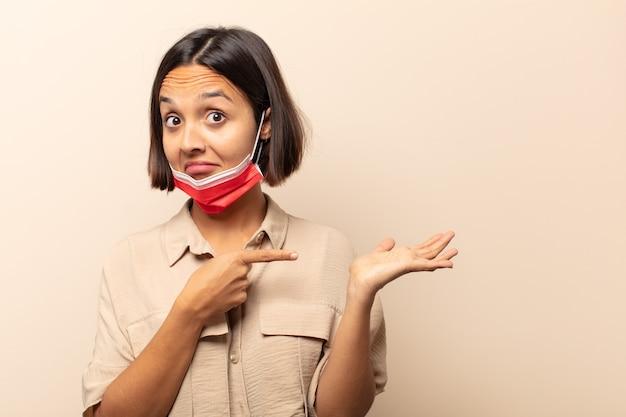 Młoda latynoska kobieta uśmiecha się radośnie i wskazuje, aby skopiować miejsce na dłoni z boku, pokazując lub reklamując przedmiot