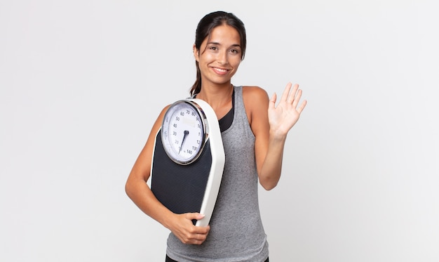 Młoda latynoska kobieta uśmiecha się radośnie, macha ręką, wita cię i wita i trzyma wagę. koncepcja diety