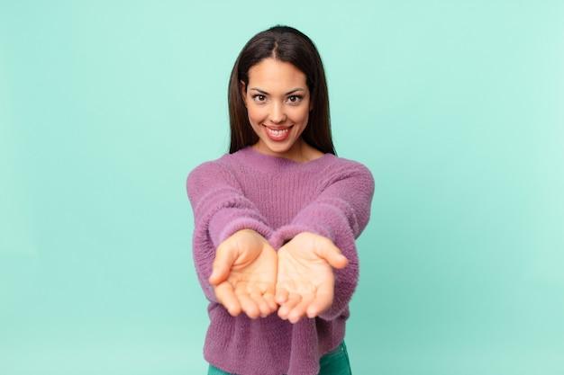 Młoda latynoska kobieta uśmiecha się radośnie z przyjazną i oferującą i pokazując koncepcję