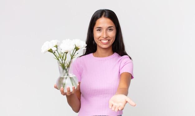 Młoda latynoska kobieta uśmiecha się radośnie z przyjazną ofertą i pokazuje koncepcję trzymającą ozdobne kwiaty