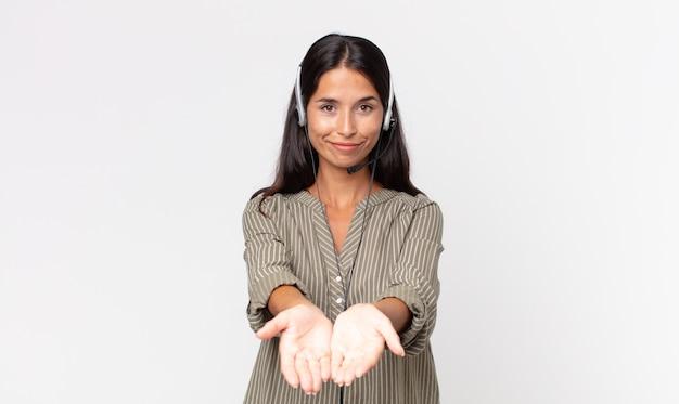 Młoda latynoska kobieta uśmiecha się radośnie z przyjazną ofertą i pokazuje koncepcję z zestawem słuchawkowym. koncepcja telemarketingu