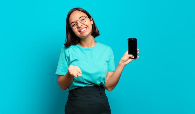 Młoda latynoska kobieta uśmiecha się radośnie z przyjaznym, pewnym siebie, pozytywnym spojrzeniem, oferuje i pokazuje przedmiot lub koncepcję