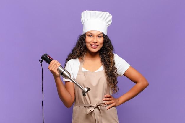 Młoda latynoska kobieta uśmiecha się radośnie, z ręką na biodrze i pewną siebie, pozytywną, dumną i przyjazną postawą. koncepcja szefa kuchni