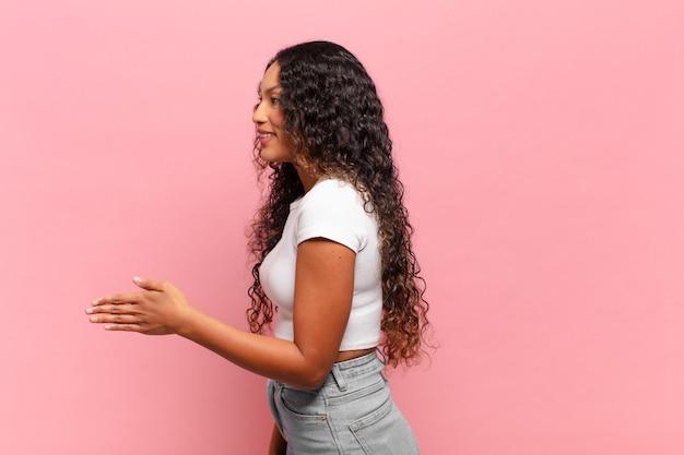 Młoda latynoska kobieta uśmiecha się, wita cię i oferuje uścisk dłoni, aby zamknąć udaną transakcję, koncepcja współpracy