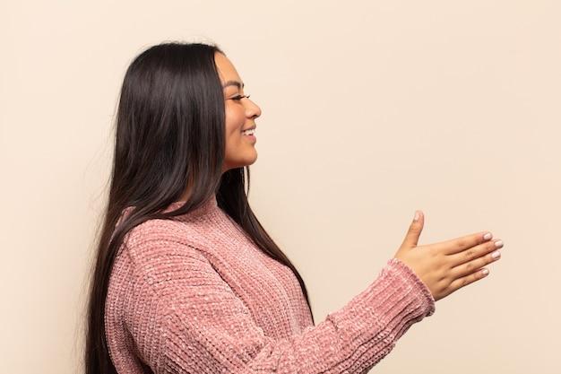 Młoda latynoska kobieta uśmiecha się, wita cię i podaje uścisk dłoni, aby zamknąć udaną transakcję