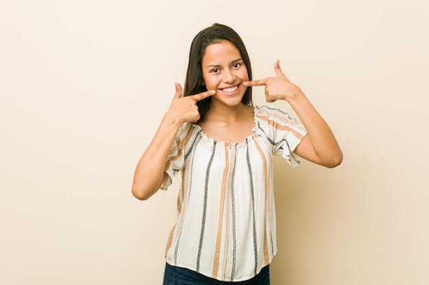 Młoda latynoska kobieta uśmiecha się, wskazując palcami na usta.