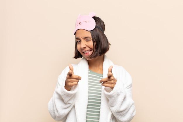 Młoda latynoska kobieta uśmiecha się z pozytywnym, udanym, szczęśliwym nastawieniem, wskazując na przód, robiąc znak pistoletu rękami
