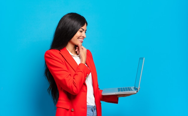 Młoda latynoska kobieta uśmiecha się z radosnym, pewnym siebie wyrazem z ręką na brodzie, zastanawia się i patrzy w bok. koncepcja laptopa