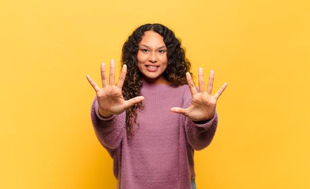 Młoda latynoska kobieta uśmiechająca się i wyglądająca przyjaźnie, pokazująca liczbę dziesięć lub dziesiątą z ręką do przodu, odliczając w dół