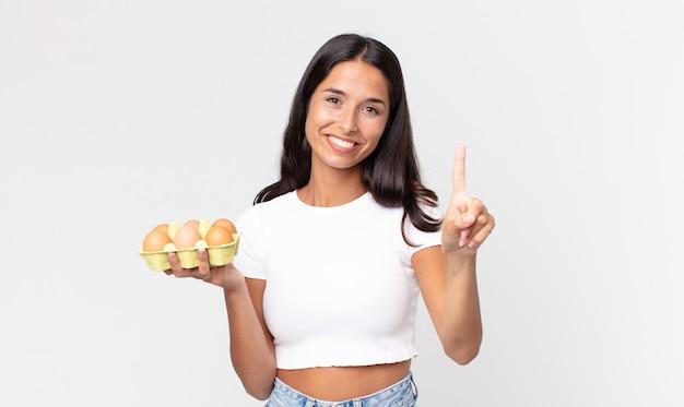 Młoda latynoska kobieta uśmiechająca się i wyglądająca przyjaźnie, pokazująca numer jeden i trzymająca pudełko z jajkami