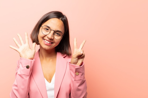 Młoda latynoska kobieta uśmiechająca się i wyglądająca przyjaźnie, pokazująca numer siedem lub siódmy z ręką do przodu, odliczając w dół