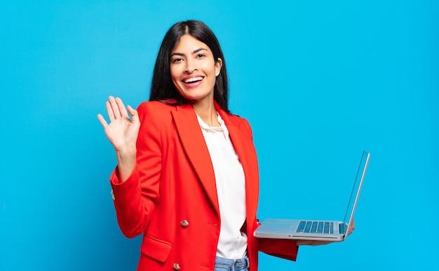 Młoda latynoska kobieta uśmiechająca się radośnie i radośnie, machająca ręką, witająca i pozdrawiająca lub żegnająca. koncepcja laptopa