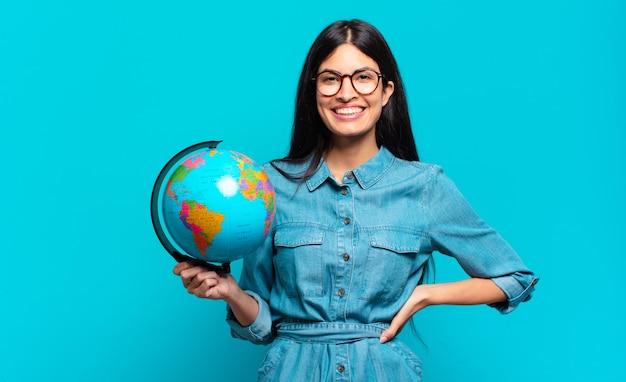 Młoda latynoska kobieta uśmiechająca się radośnie z ręką na biodrze i pewna siebie, pozytywna, dumna i przyjazna