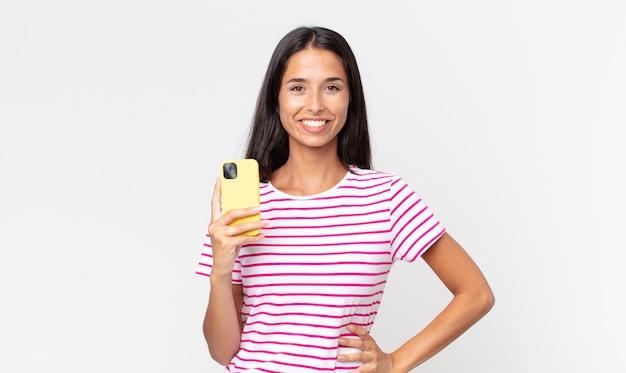 Młoda latynoska kobieta uśmiechająca się radośnie z ręką na biodrze i pewna siebie, trzymająca smartfona
