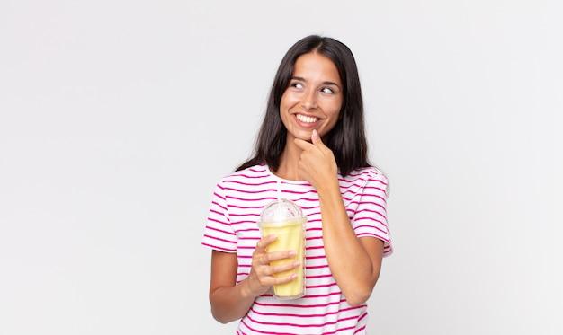 Młoda latynoska kobieta uśmiechająca się ze szczęśliwym, pewnym siebie wyrazem twarzy z ręką na brodzie i trzymająca koktajl mleczny o smaku waniliowym