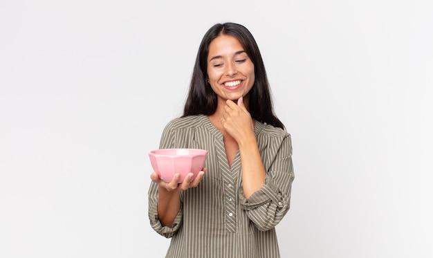 Młoda latynoska kobieta uśmiechająca się ze szczęśliwym, pewnym siebie wyrazem twarzy z ręką na brodzie i trzymająca pustą miskę lub garnek