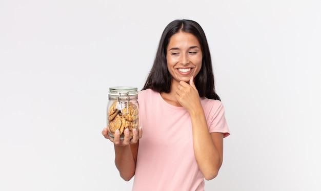 Młoda latynoska kobieta uśmiechająca się ze szczęśliwym, pewnym siebie wyrazem twarzy z ręką na brodzie i trzymająca szklaną butelkę po ciastkach