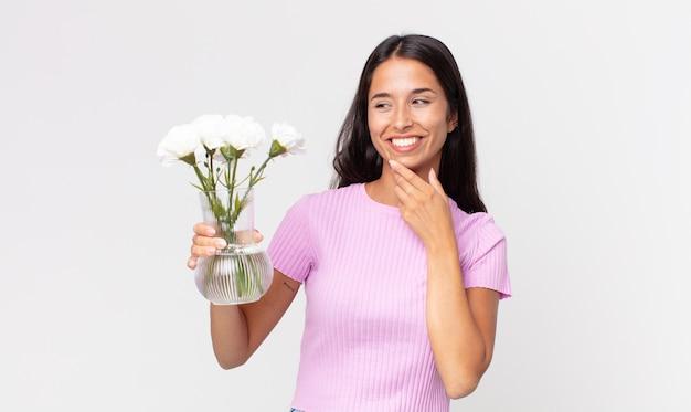 Młoda latynoska kobieta uśmiechająca się ze szczęśliwym, pewnym siebie wyrazem twarzy z ręką na brodzie, trzymająca ozdobne kwiaty