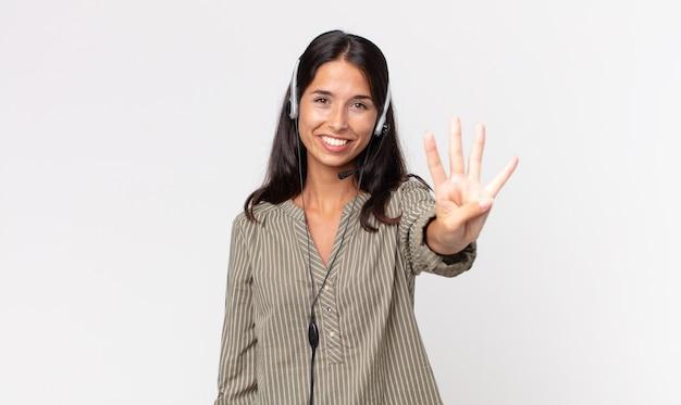 Młoda latynoska kobieta uśmiechnięta i patrząca przyjaźnie, pokazująca numer cztery z zestawem słuchawkowym. koncepcja telemarketingu