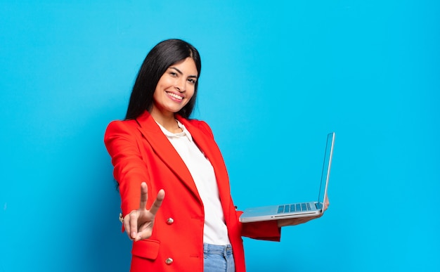 Młoda latynoska kobieta uśmiechnięta i wyglądająca na szczęśliwą, beztroską i pozytywną, gestykulującą jedną ręką zwycięstwo lub pokój