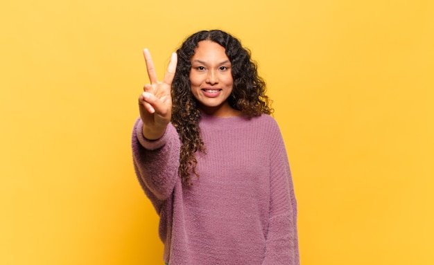 Młoda latynoska kobieta uśmiechnięta i wyglądająca przyjaźnie, pokazująca cyfrę dwa lub drugą z ręką do przodu, odliczając w dół