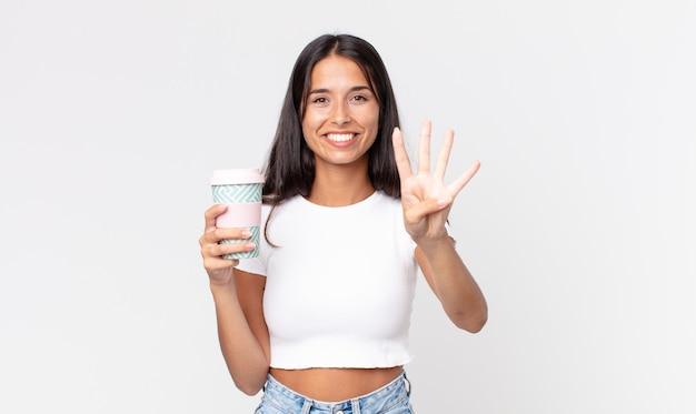 Młoda latynoska kobieta uśmiechnięta i wyglądająca przyjaźnie, pokazująca numer cztery i trzymająca pojemnik na kawę na wynos