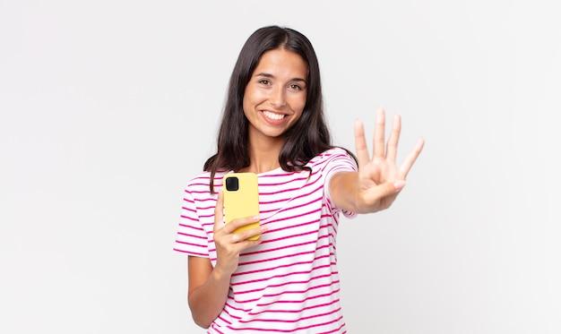 Młoda latynoska kobieta uśmiechnięta i wyglądająca przyjaźnie, pokazująca numer cztery i trzymająca smartfona