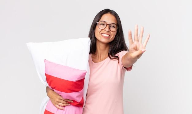 Młoda latynoska kobieta uśmiechnięta i wyglądająca przyjaźnie, pokazująca numer cztery w piżamie i trzymająca poduszkę