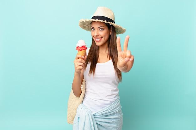 Młoda latynoska kobieta uśmiechnięta i wyglądająca przyjaźnie, pokazująca numer dwa i trzymająca lody. koncepcja suma