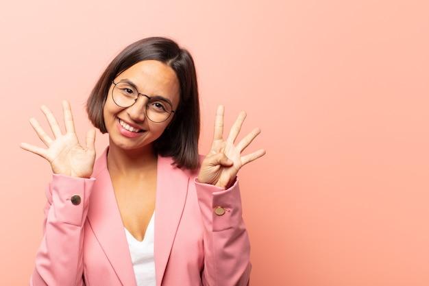 Młoda latynoska kobieta uśmiechnięta i wyglądająca przyjaźnie, pokazująca numer dziewięć lub dziewiąty z ręką do przodu, odliczając w dół