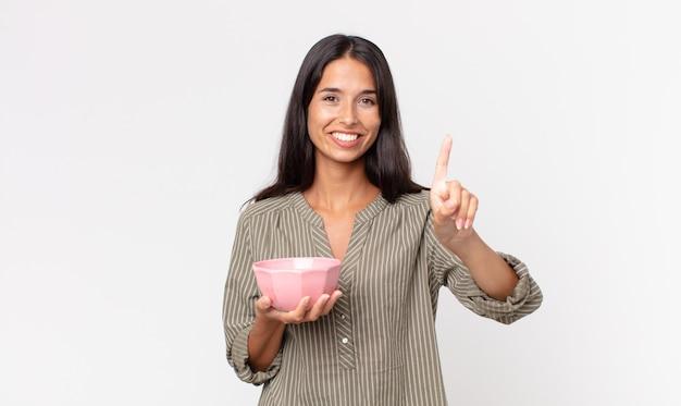 Młoda latynoska kobieta uśmiechnięta i wyglądająca przyjaźnie, pokazująca numer jeden i trzymająca pustą miskę lub garnek